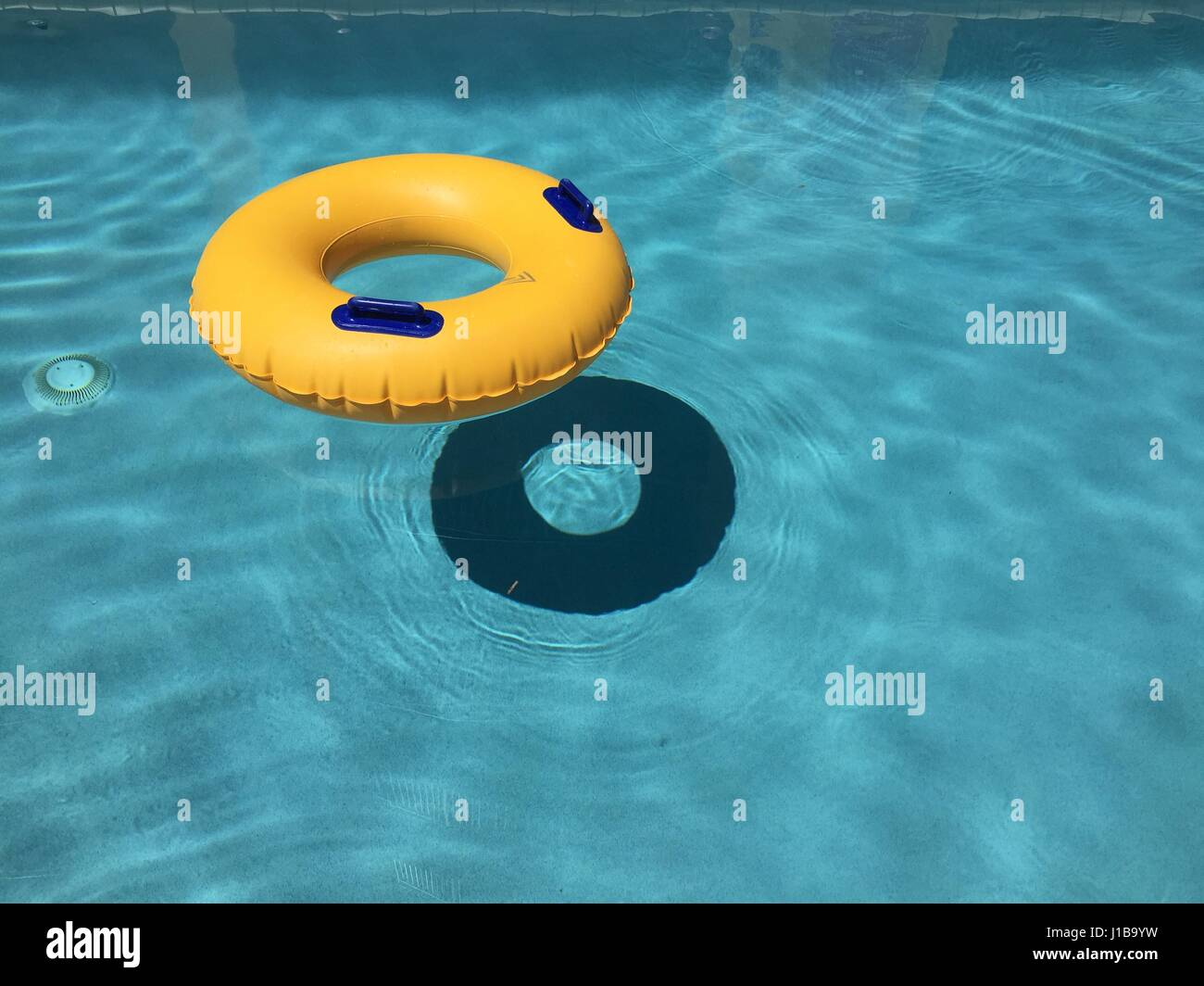 Yellow pool float / ring floating in a swimming pool Stock Photo ...