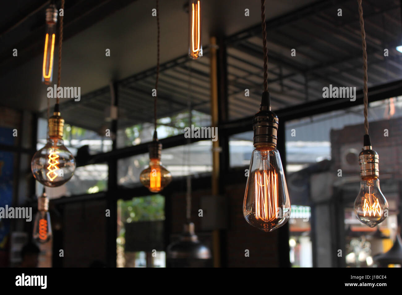 Set of glowing light bulbs hang on ceiling - Stock Image