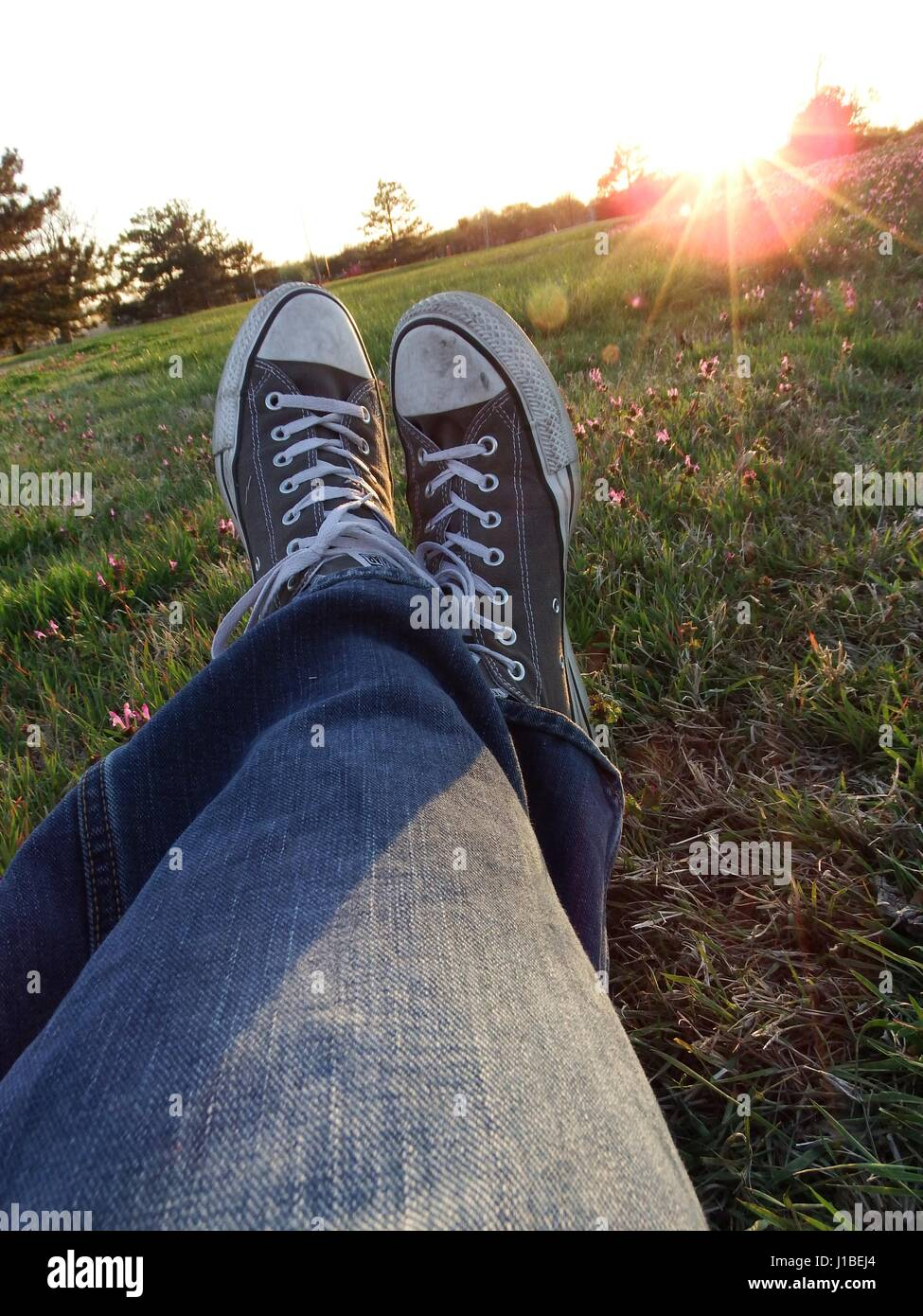 A pov view of shoes sitting in the grass as