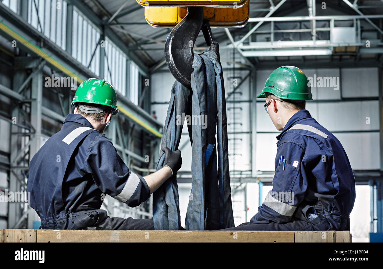 Men preparing large machine part for crane lifting. Heavy Industry, Heavy Lifting, Engineering, employment, 'Men - Stock Image