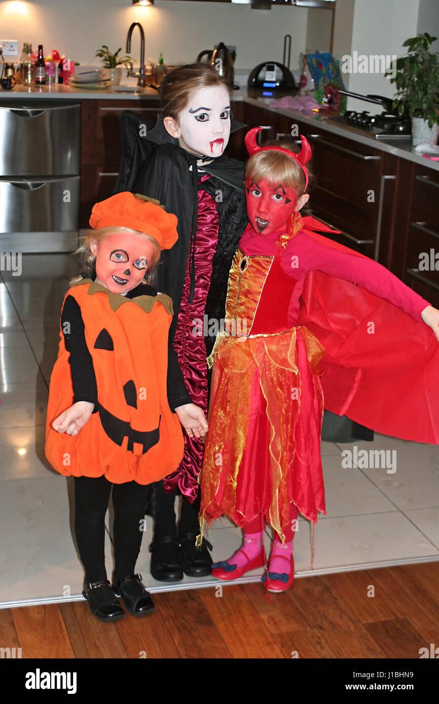 Girls children wearing halloween costumes trick or treat devil pumpkin dracula fancy dress kids family  sc 1 st  Alamy & Girls children wearing halloween costumes trick or treat devil ...