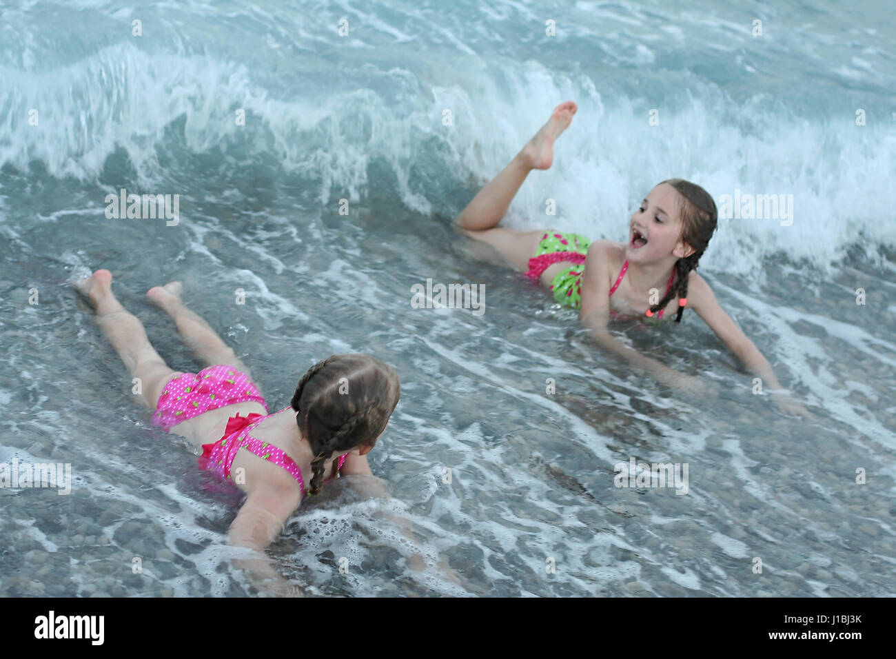 Sisters, children having great fun playing in white foamy waves on a stony beach at sunset, happiness concept, joy - Stock Image
