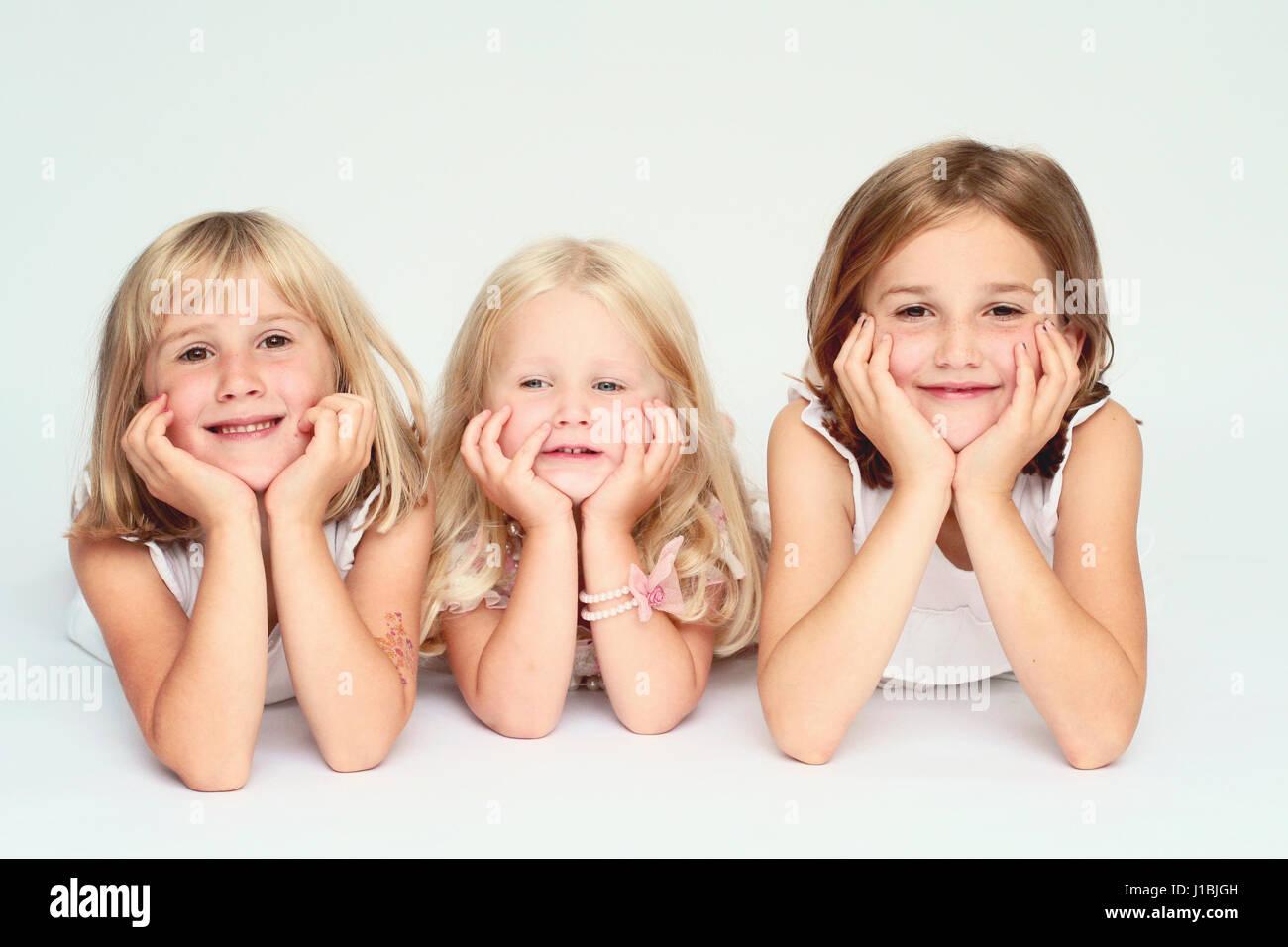 Three sisters portrait lying on their tummies, blonde family, joyful happy family concept - Stock Image