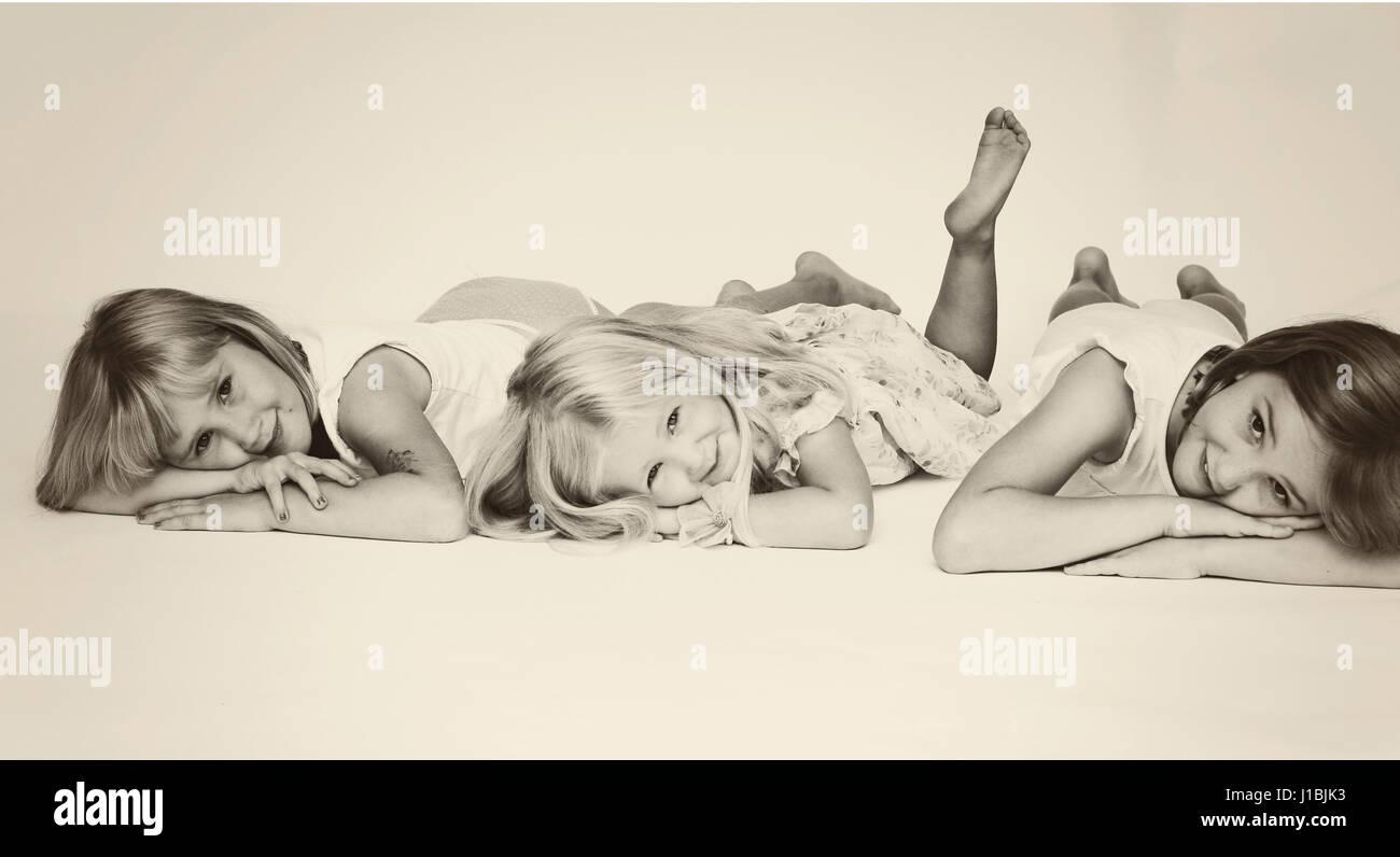 Three sisters portrait lying on their tummies - Stock Image