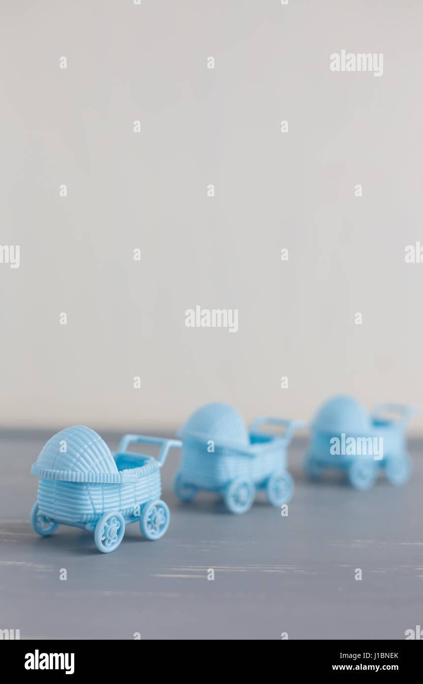 A row of three blue baby carriages with emphasis on the first. - Stock Image