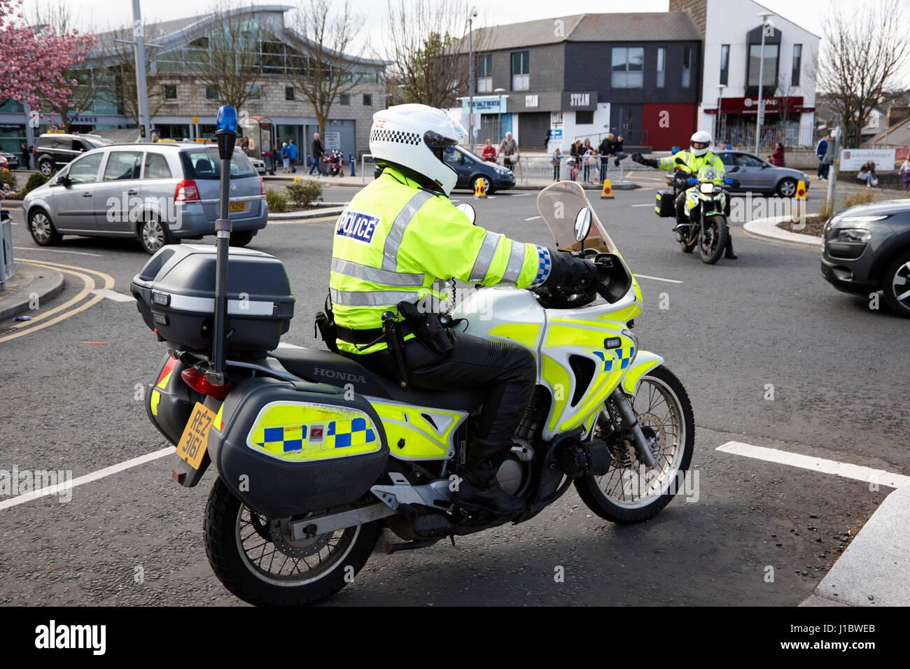 psni police officer traffic police on honda motorbike directing traffic at roundabout northern ireland - Stock Image