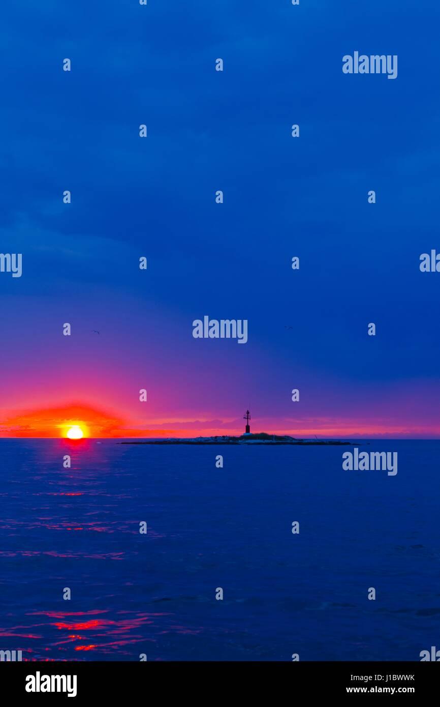 Sunset at sea lighthouse silhouette small tiny island before Porec in Croatia Stock Photo