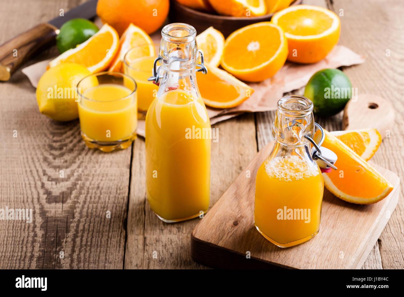 Freshly squeezed orange juice in bottles against the background of fresh  citrus fruits - Stock Image