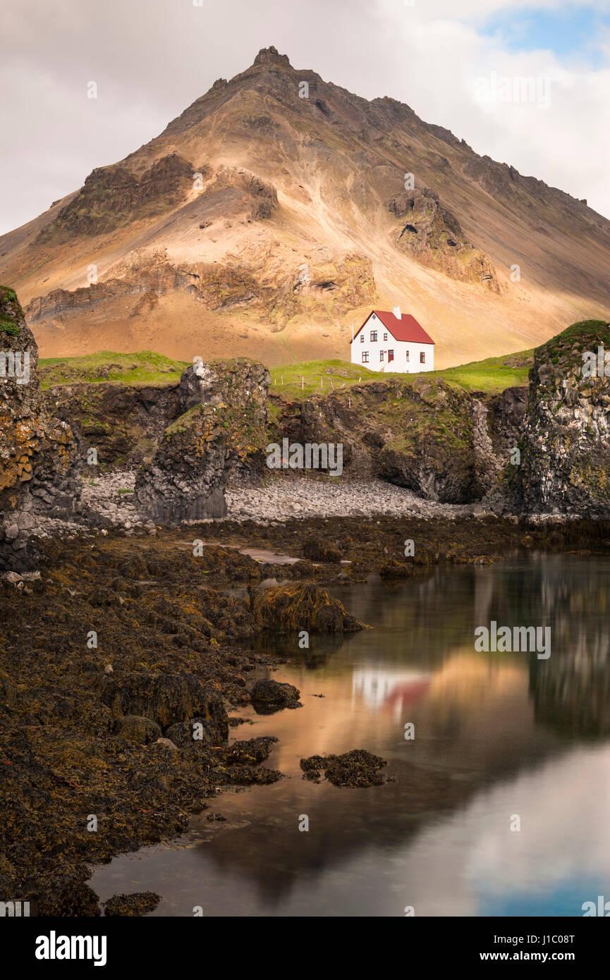 Arnarstapi, icelandic fishing village, oceanside white farm house over lava rocks, Stapafell mountain, Snæfellsnes - Stock Image