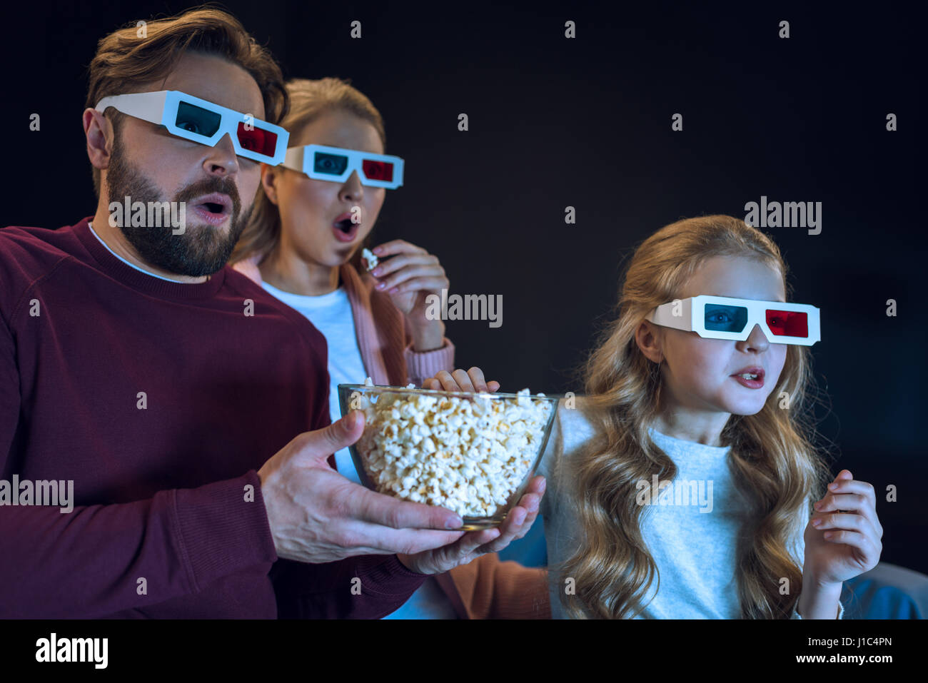 Shocked family in 3d glasses watching movie and eating popcorn - Stock Image