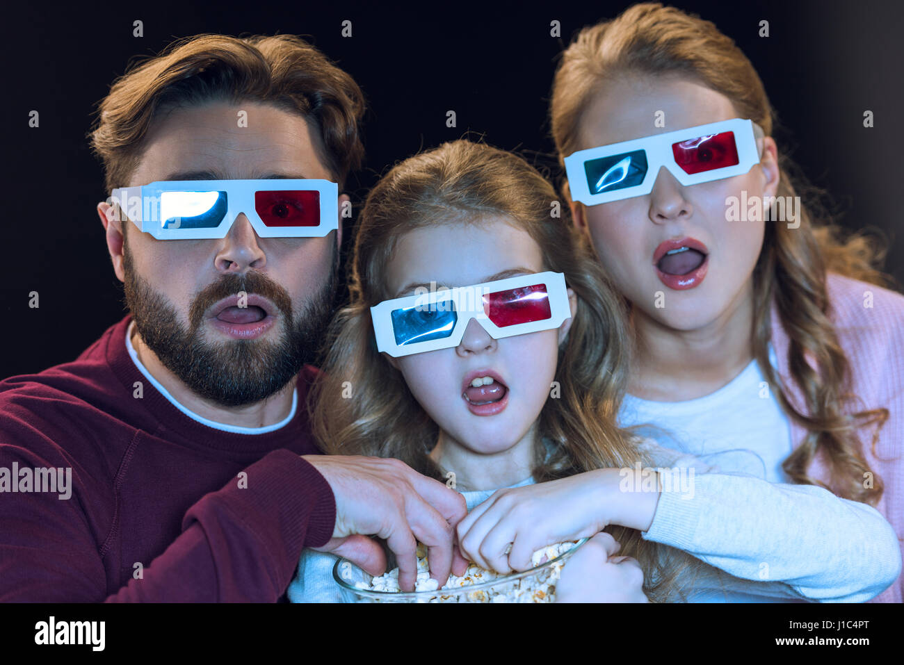 Shocked family in 3d glasses watching movie and eating popcorn from bowl - Stock Image