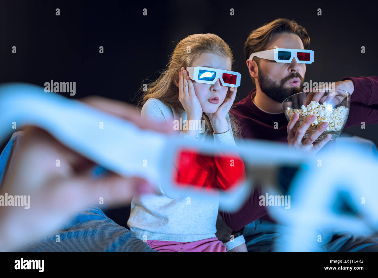 Shocked father and daughter in 3d glasses watching movie and eating popcorn - Stock Image