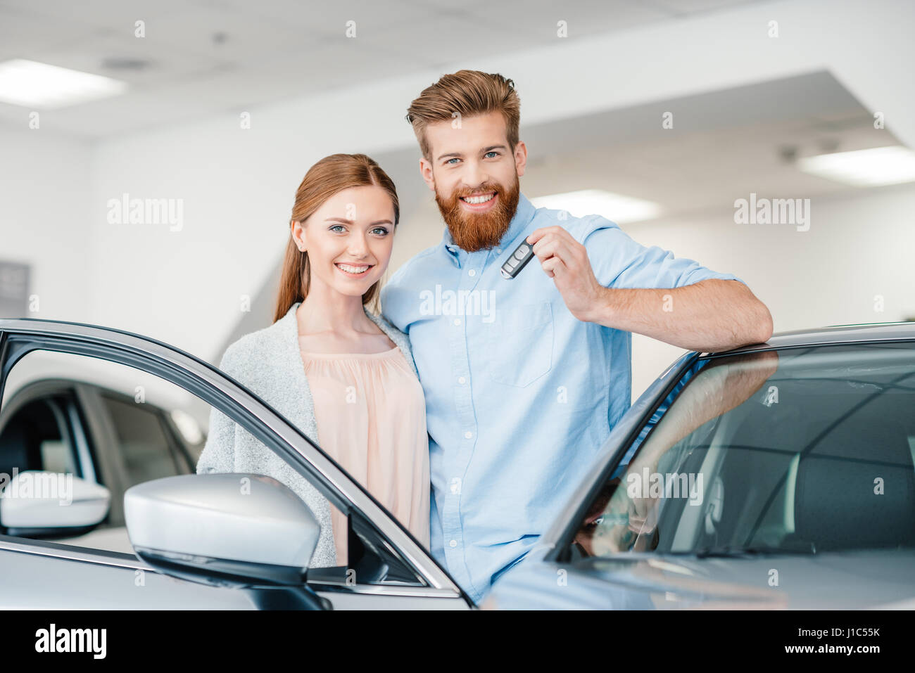 Key Car Dealership >> Happy Couple Holding Car Key And Standing At Car In Dealership Salon