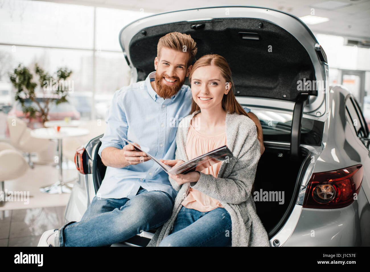 Happy couple with catalog sitting on car trunk in dealership salon - Stock Image