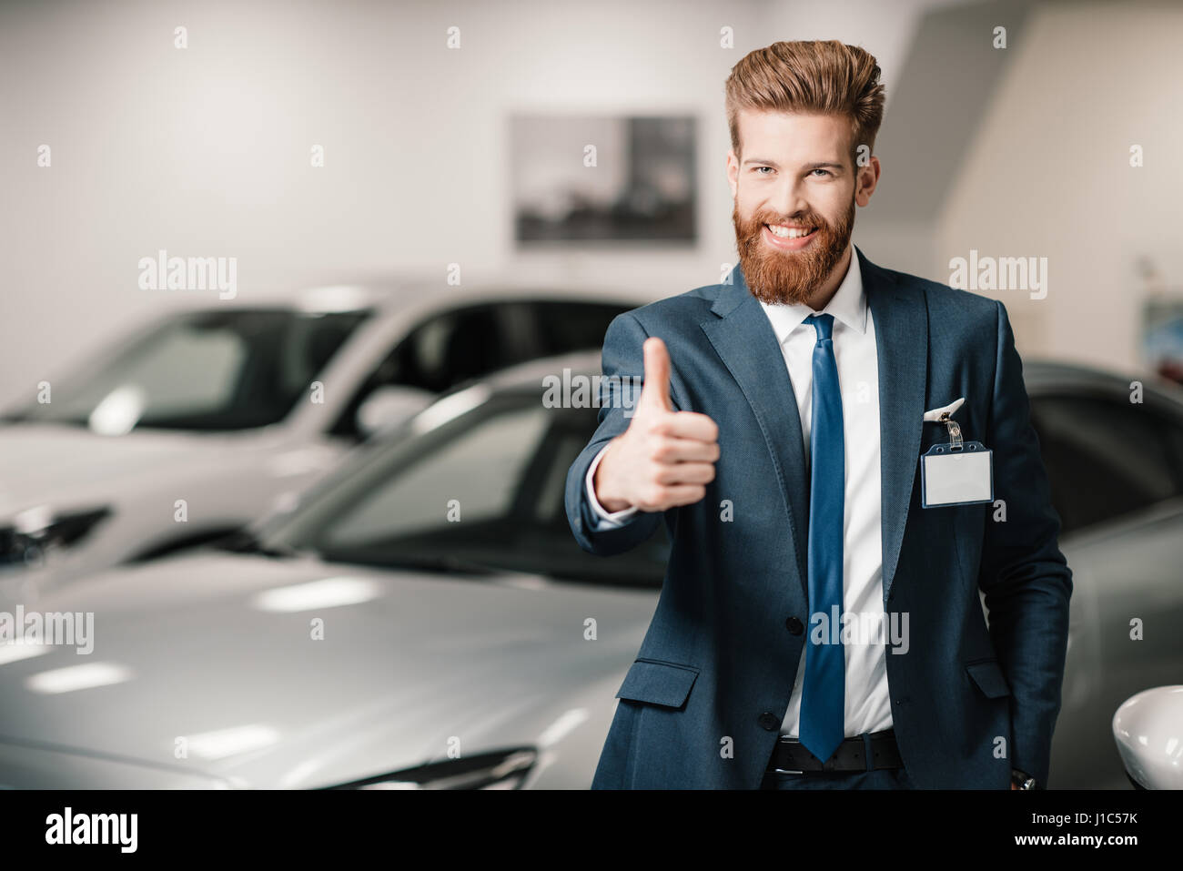 salesman in suit showing thumb up and looking at camera in dealership salon - Stock Image