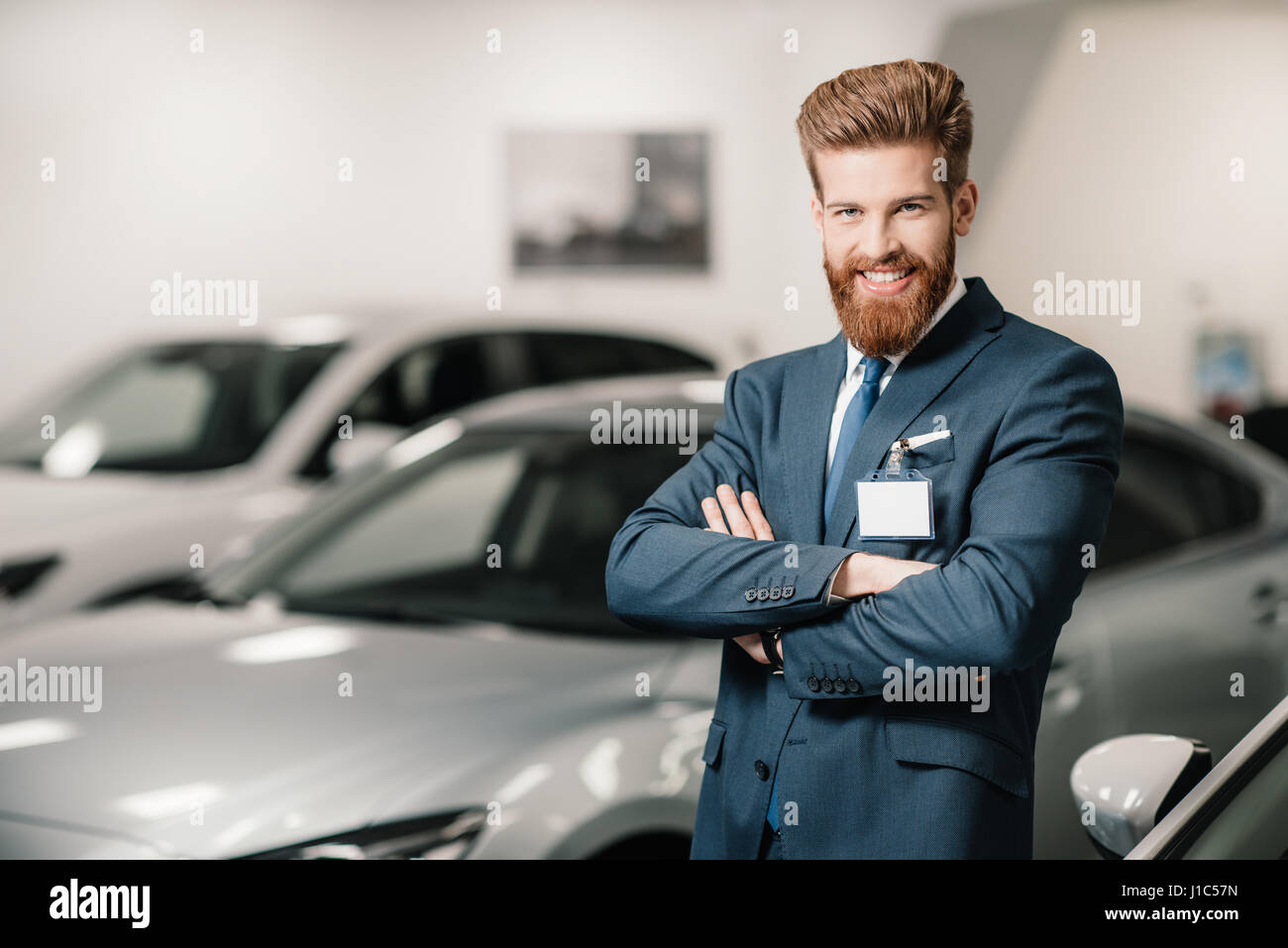 salesman in suit with crossed arms posing and looking at camera in dealership salon - Stock Image