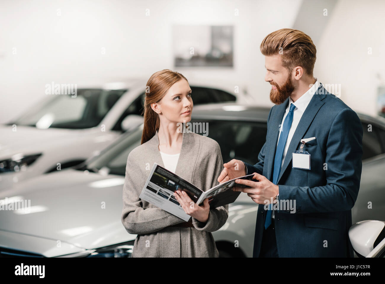 salesman in suit showing catalog to customer in dealership salon - Stock Image