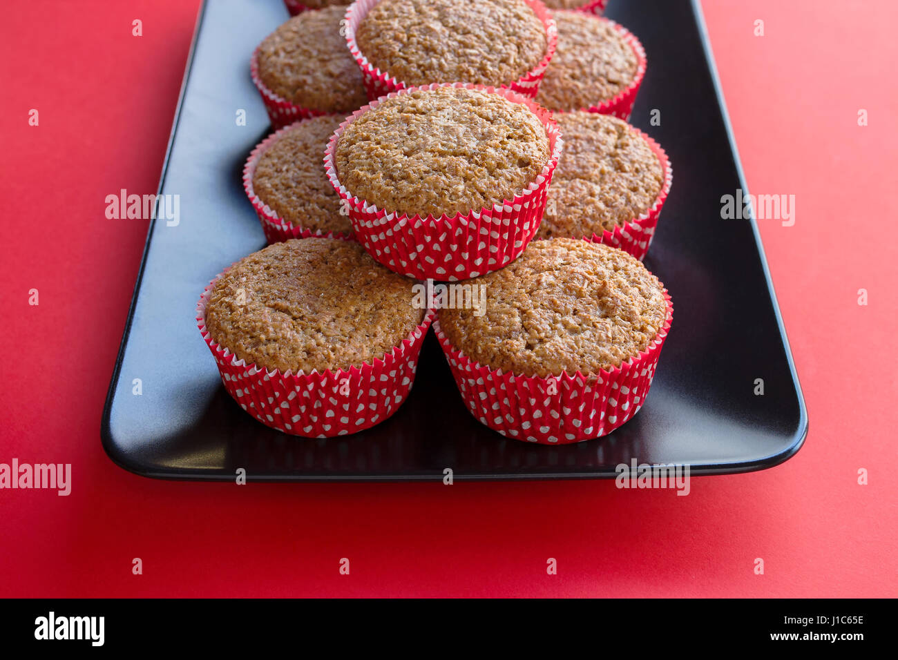 Bran muffins in bright red and white paper holders on a black rectangular plate and red background Stock Photo