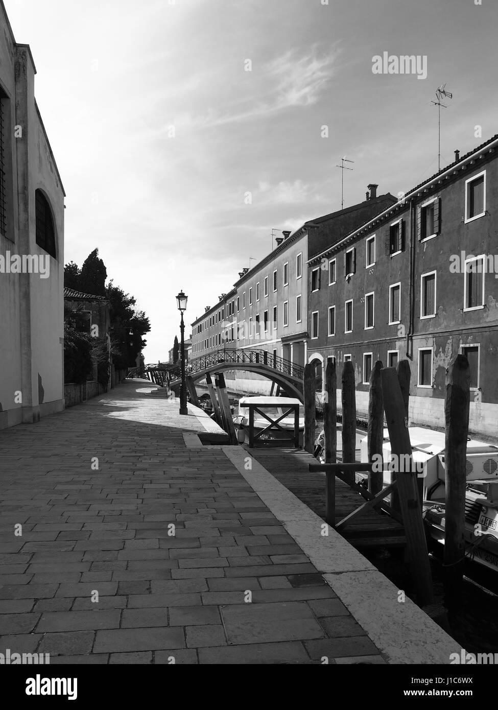 canal path with pavement lamp post and boats in guidecca in venice - Stock Image