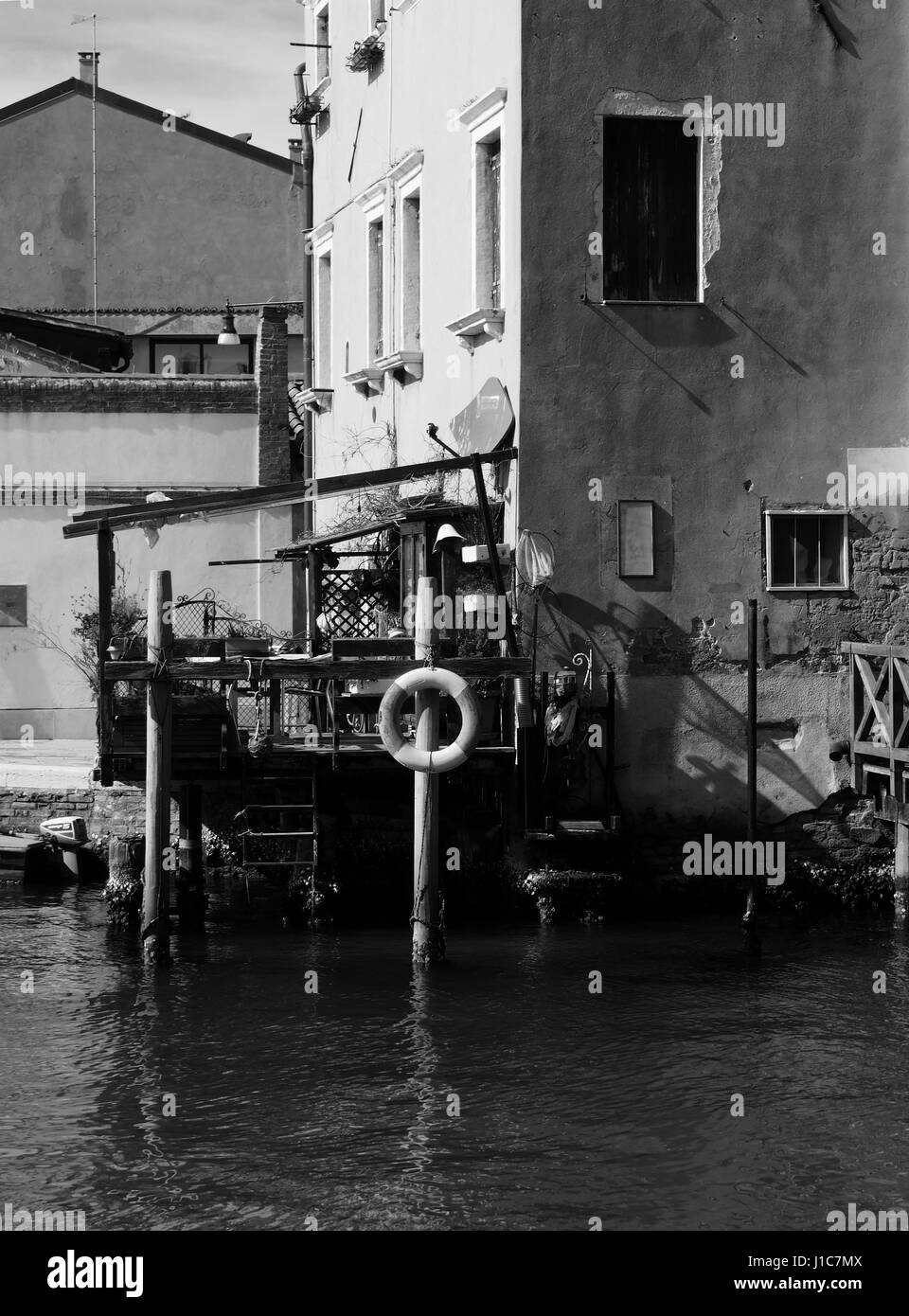 life preserver and boat details at the side of a canal in guidecca in venice - Stock Image