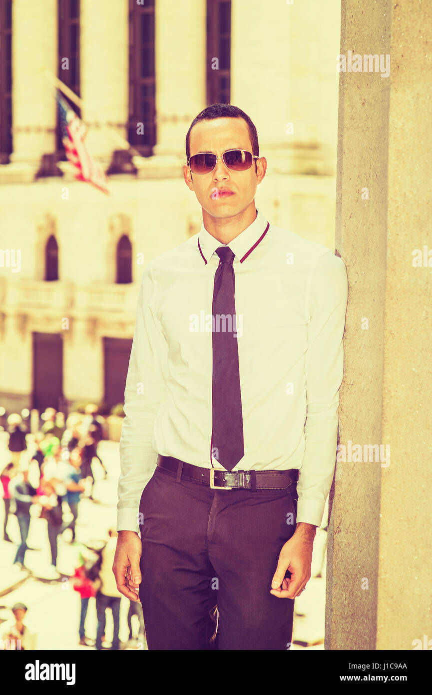 Young American Businessman traveling, working in New York, wearing white shirt, black tie, sunglasses, standing - Stock Image