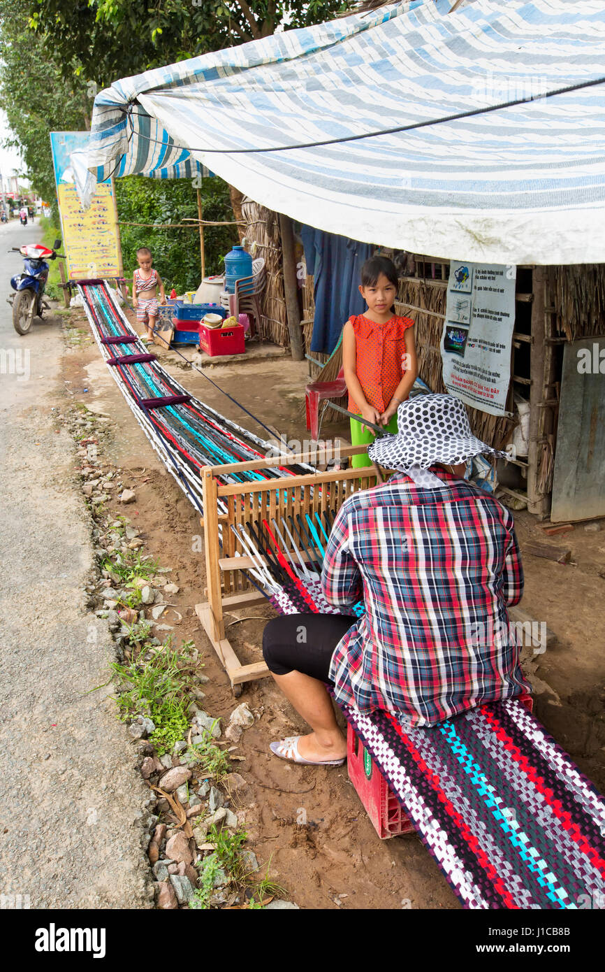 Woman working at loom, weaving extended rug  (18 meters) to be sectioned into smaller lengths, young daughter & - Stock Image