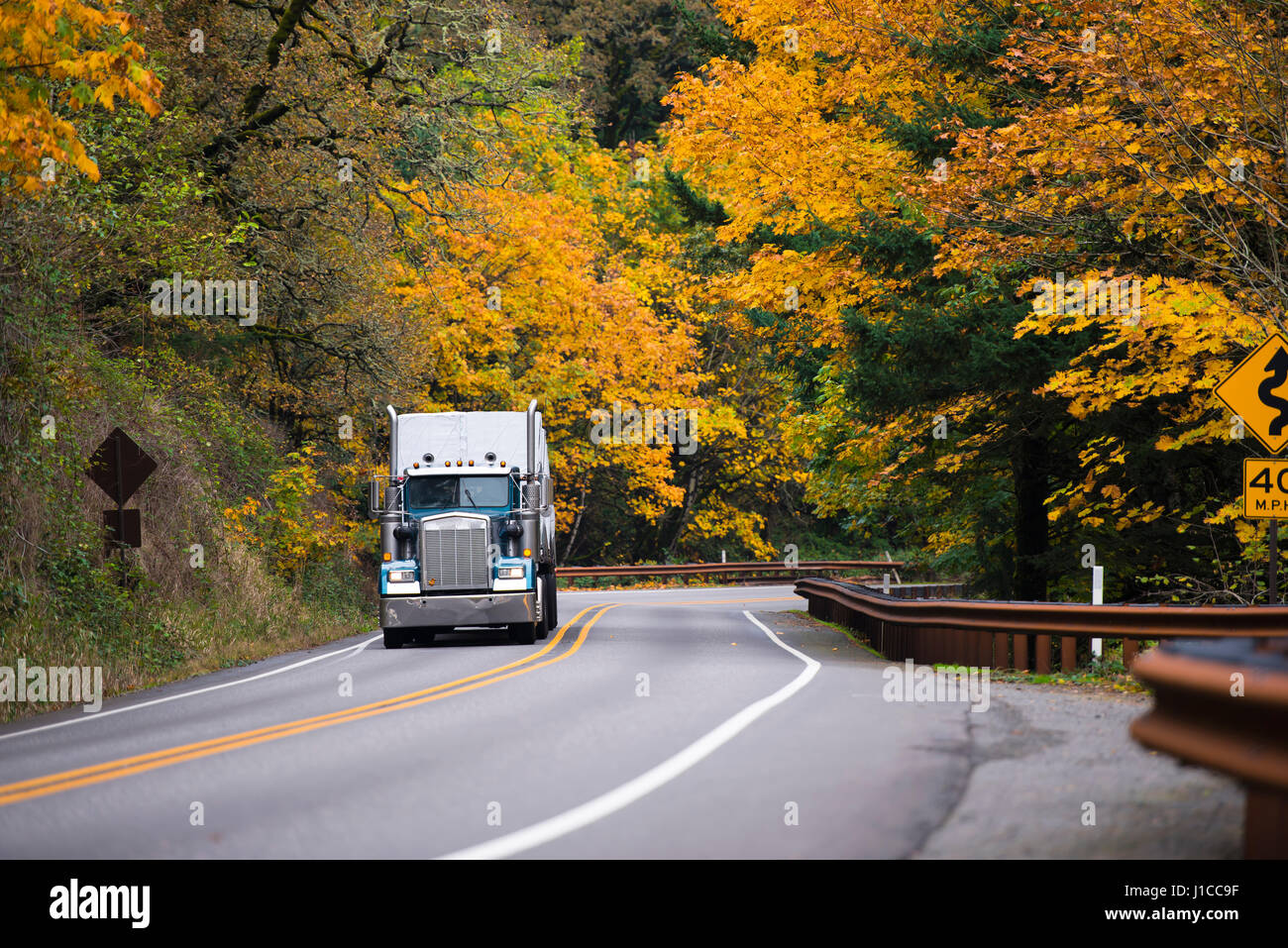 Large cool classic semi truck with chrome accents and high tailpipes and a trailer on a scenic road with twists, - Stock Image