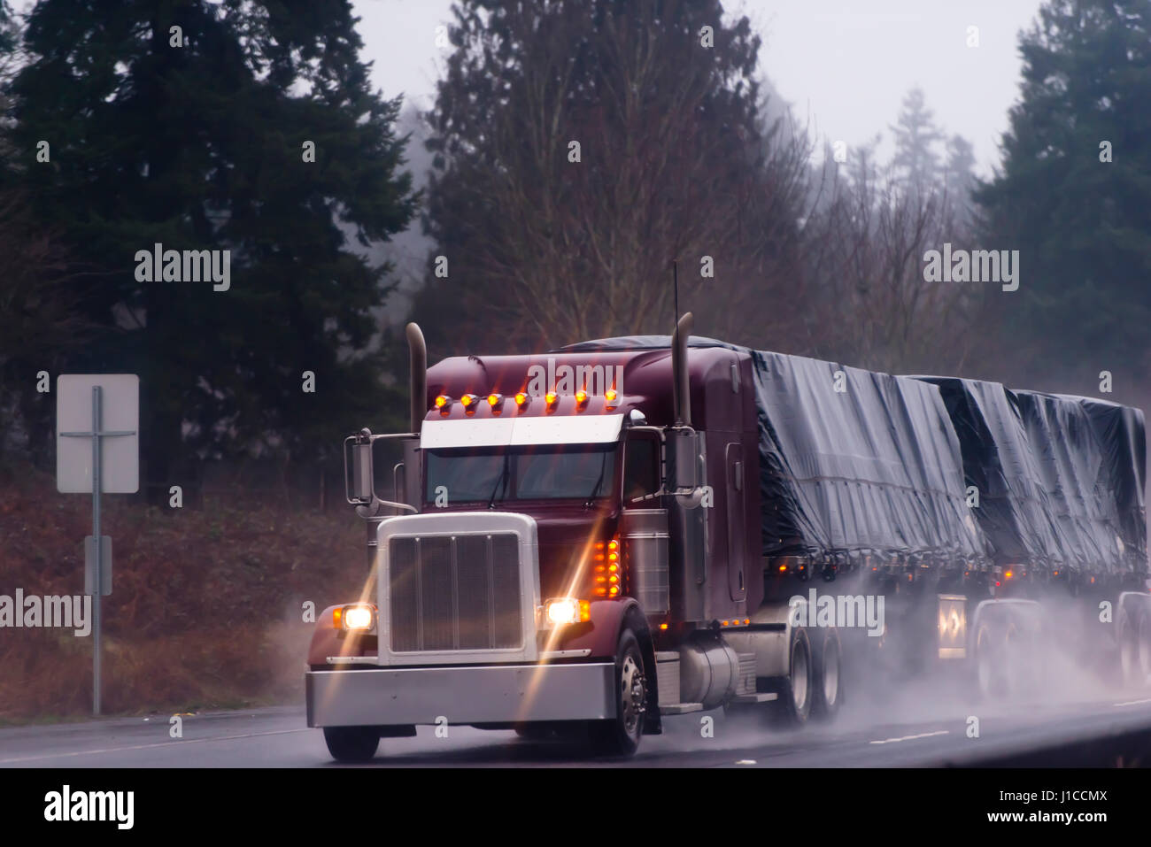 Big nice classic burgundy rig semi truck with lights and flat bad frailer with black turp  in rain on high way on - Stock Image