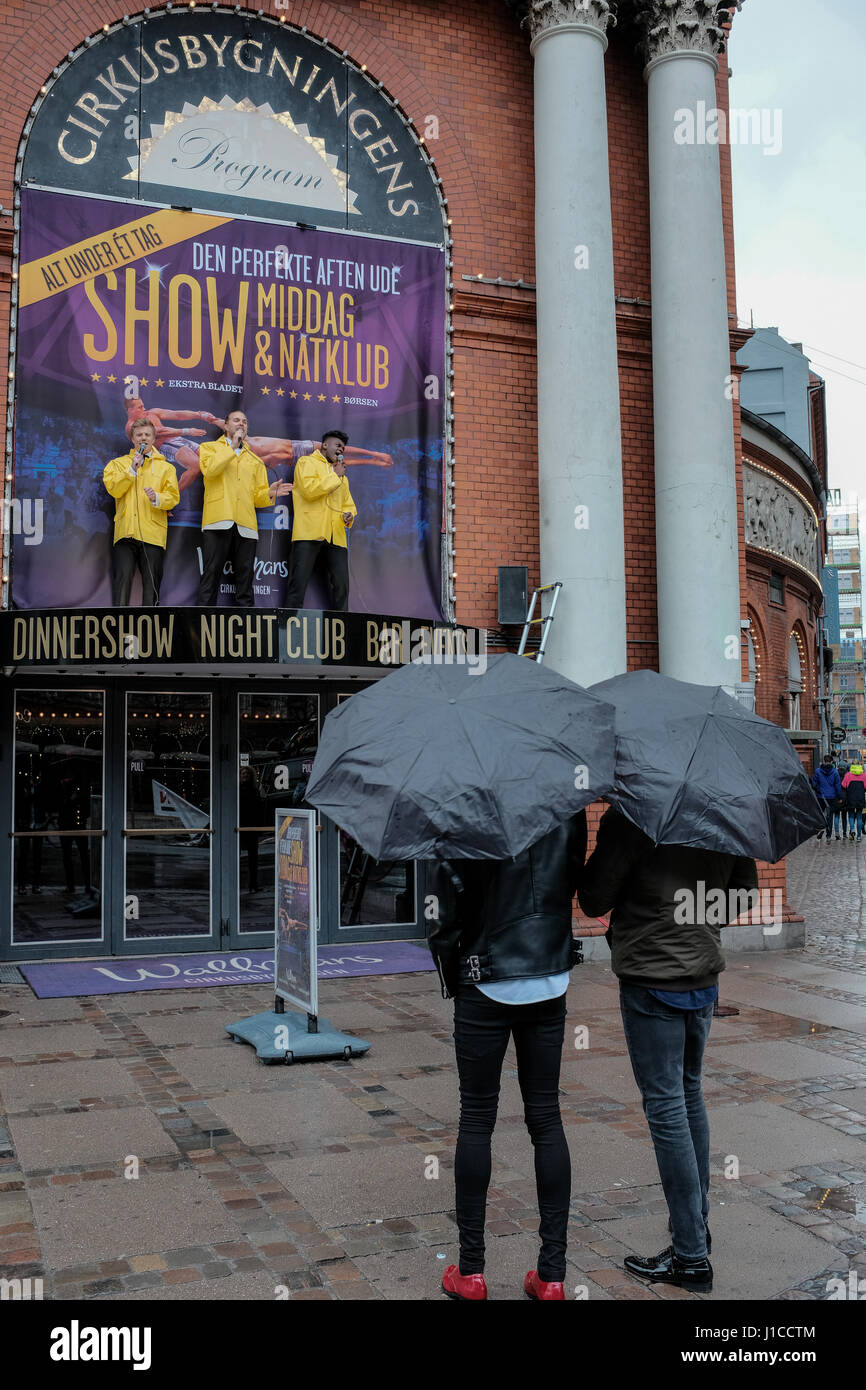 Singing in the rain, three entertainers in yellow raincoats promoting a show at Cirkusbygningen, a 19th century - Stock Image