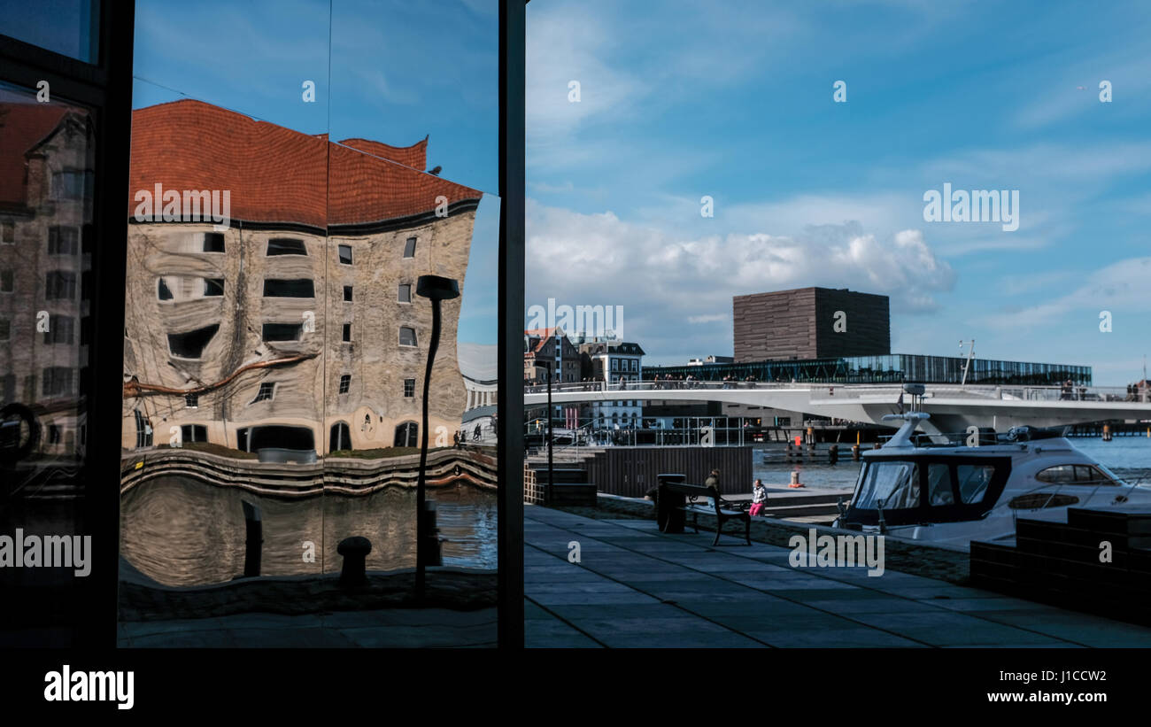Distorted reflection of old Noma restaurant building in new Krøyers Plads development with Inderhavnen bridge and Royal Danish Playhouse in background Stock Photo
