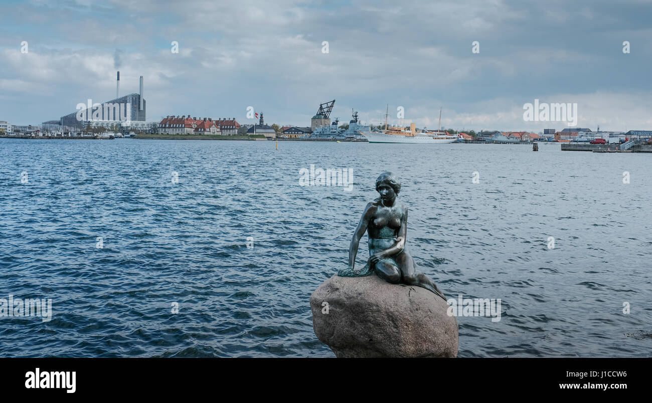 The Little Mermaid with The Royal Yacht Dannebrog moored on the other side of the harbour, Copenhagen, Denmark - Stock Image