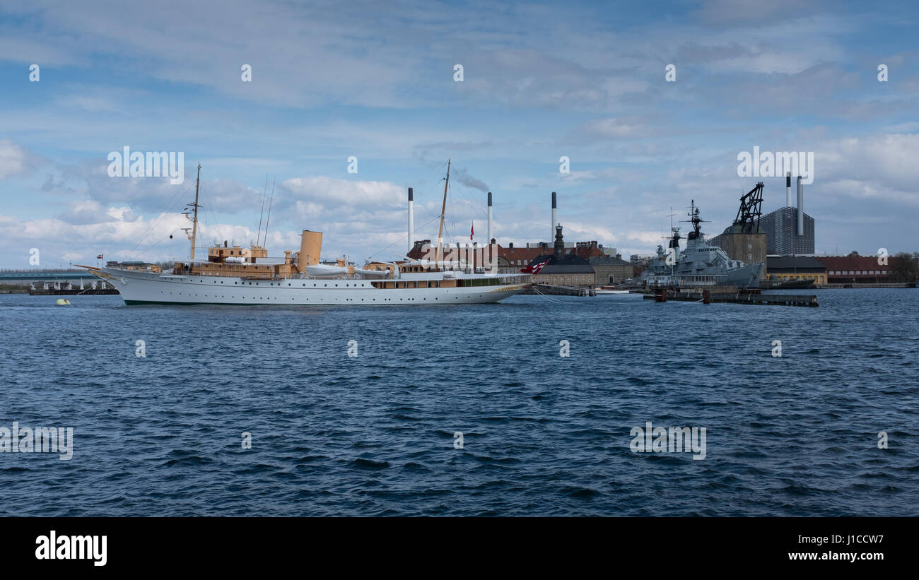 The Royal Yacht Dannebrog moored in copenhagen harbour with the waste to energy plant, Amager Bakke, in the background. - Stock Image