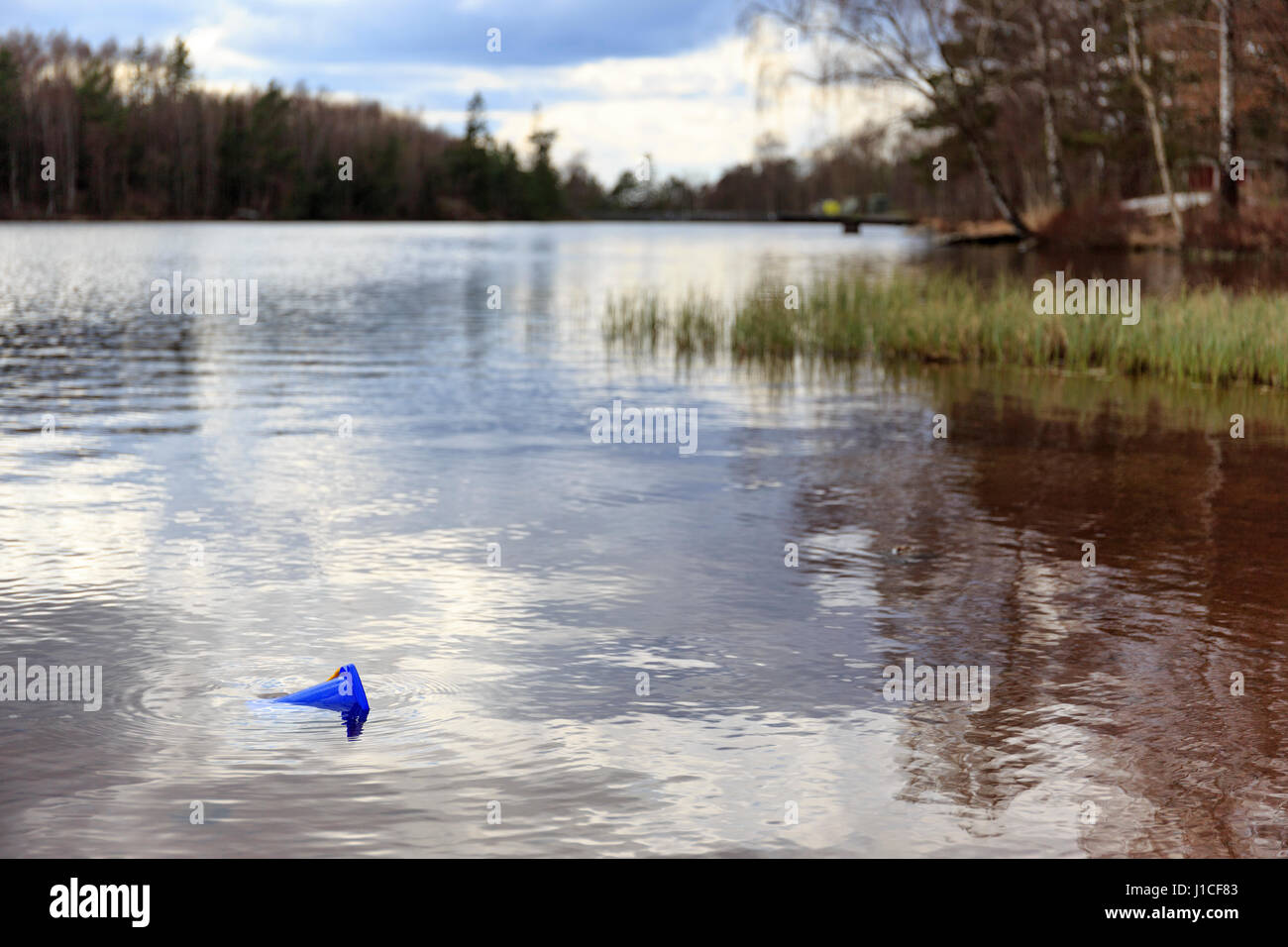 Blue sand bucket left behind in water by empty deserted lake beach  Model Release: No.  Property Release: No. - Stock Image