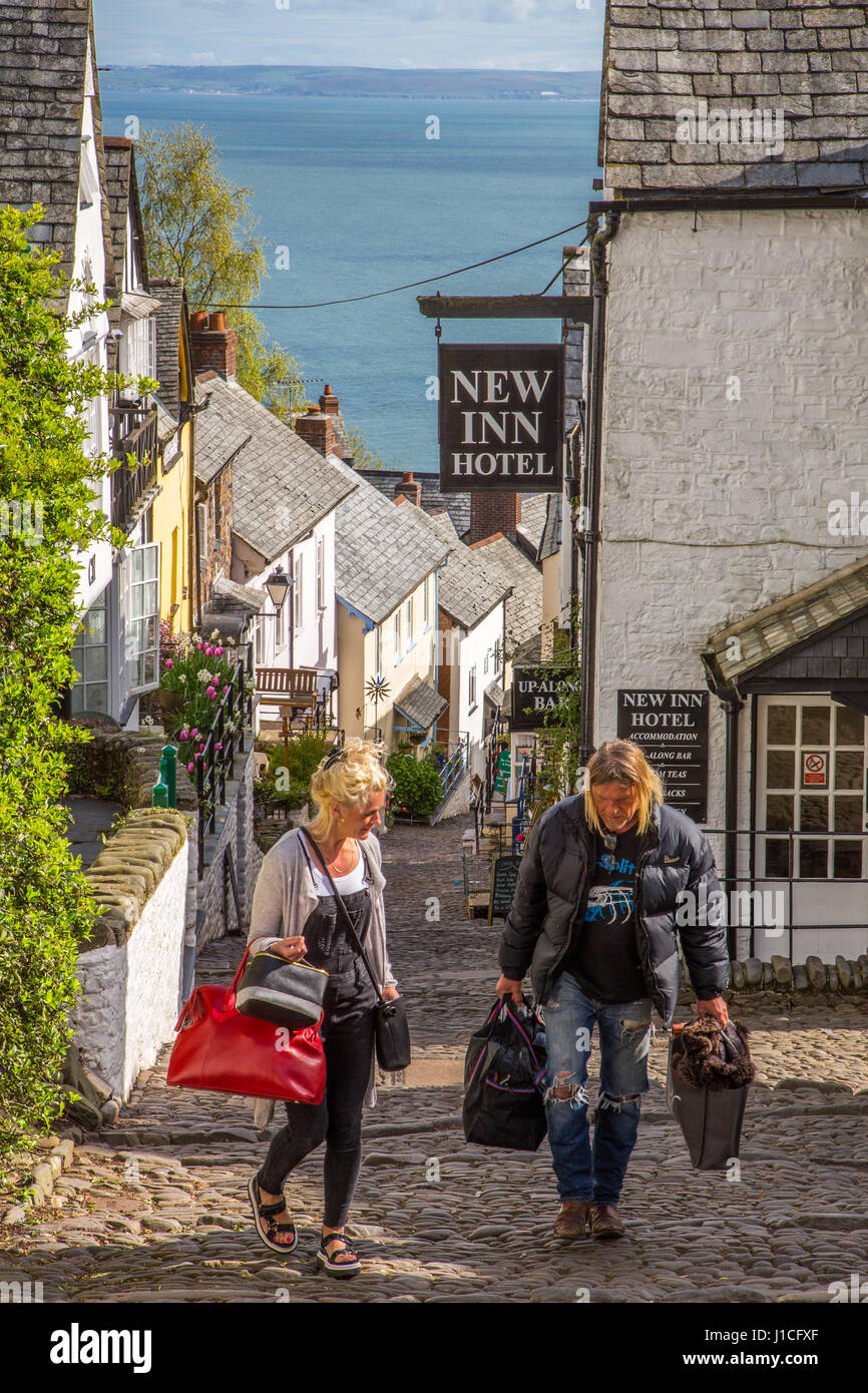 Clovelly,North Devon, UK, guests with suitcases walking up the steep cobbled street after checking out of the New - Stock Image