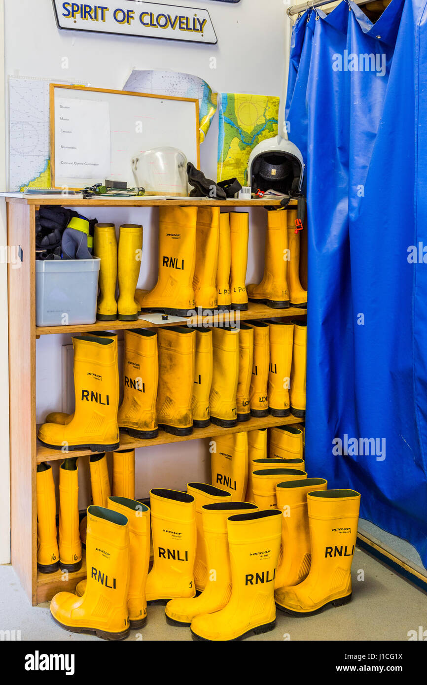 RNLI, Clovelly, North Devon,UK . The Spirit of Clovelly in shore lifeboat crewroom yellow crew boots neatly stowed - Stock Image