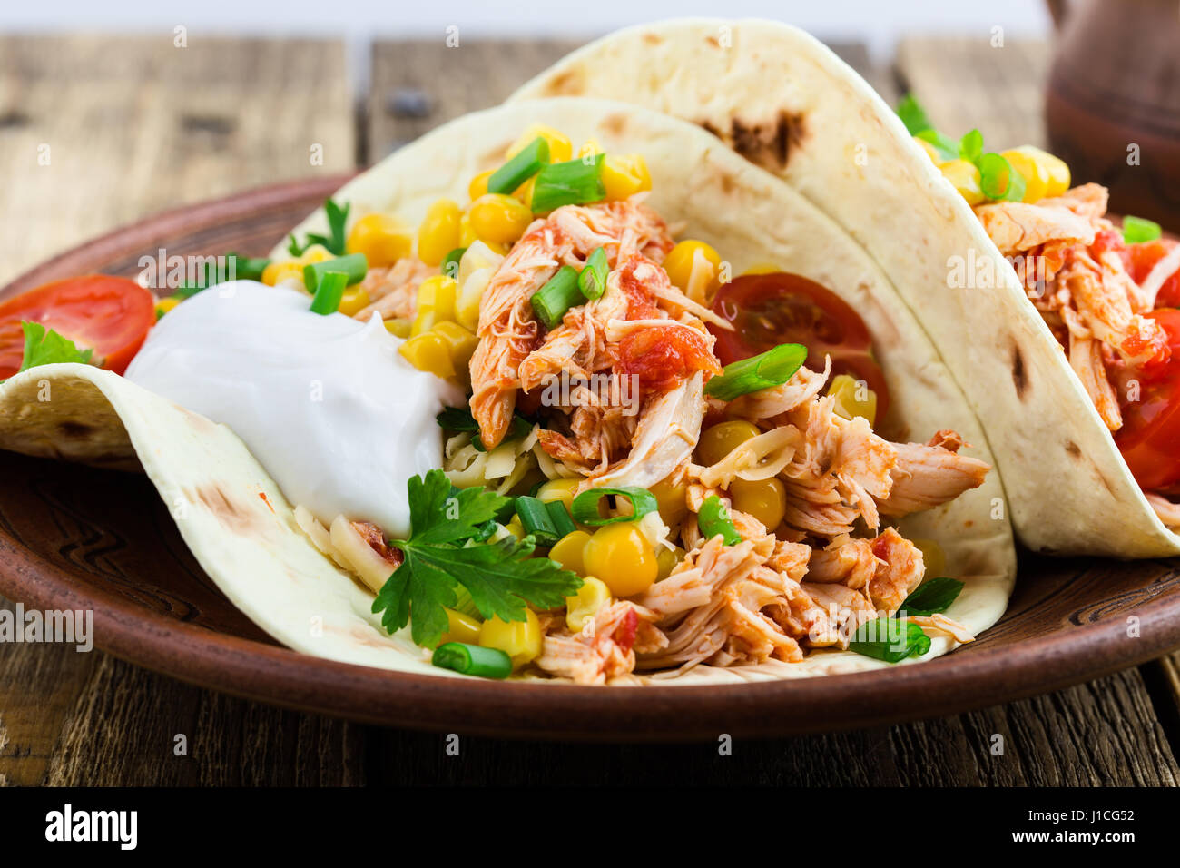 Homemade slow cooker chicken taco with corn served on rustic ceramic plate on wooden table, mexican style - Stock Image