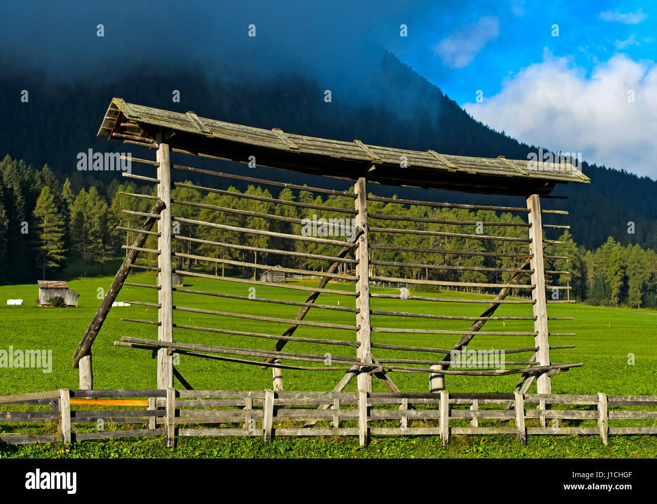 Traditional single straight-line hayrack on an alm, Sexten, South Tyrol, Italy - Stock Image