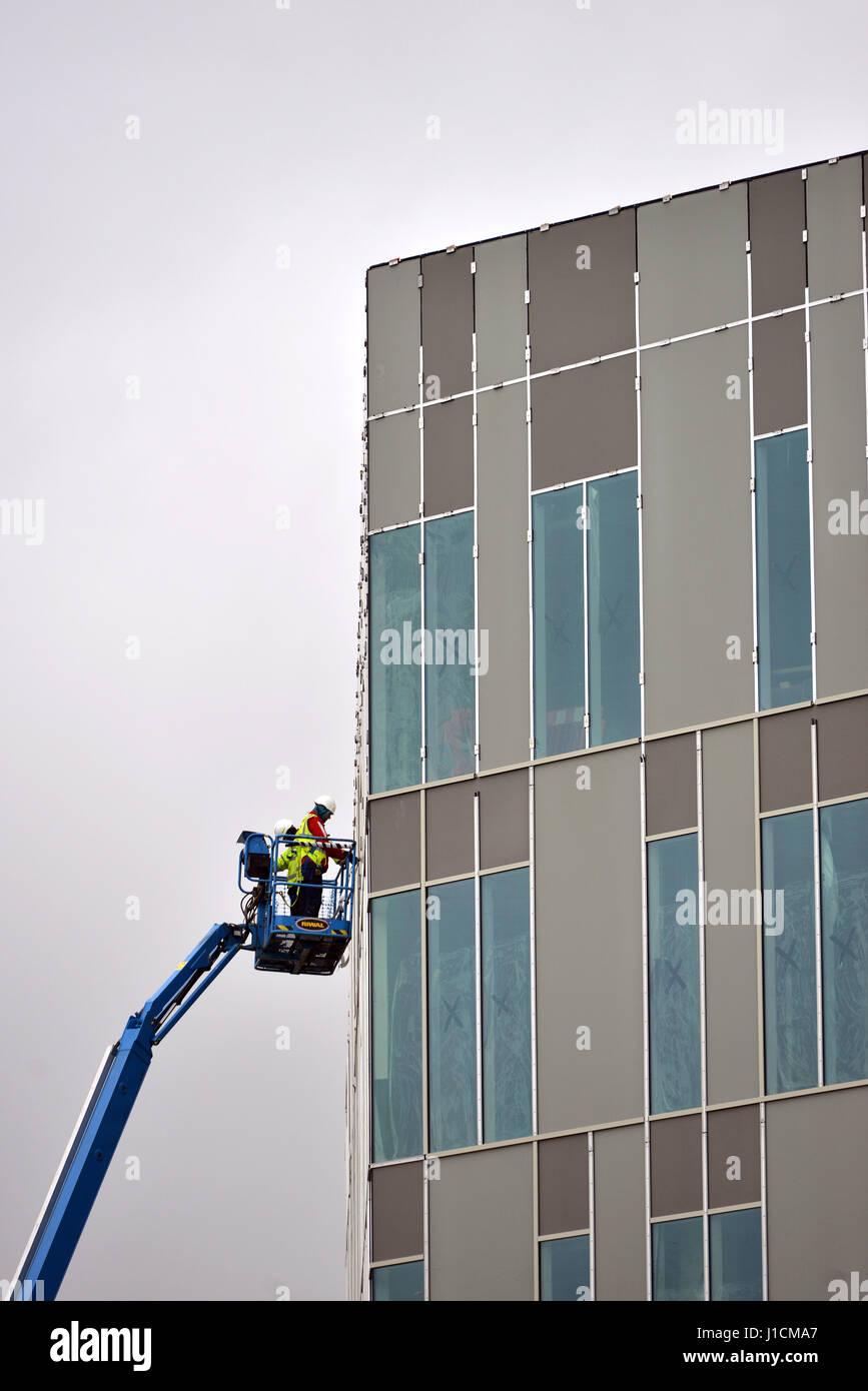 Workmen in a cherry picker platform working on a modern building. - Stock Image