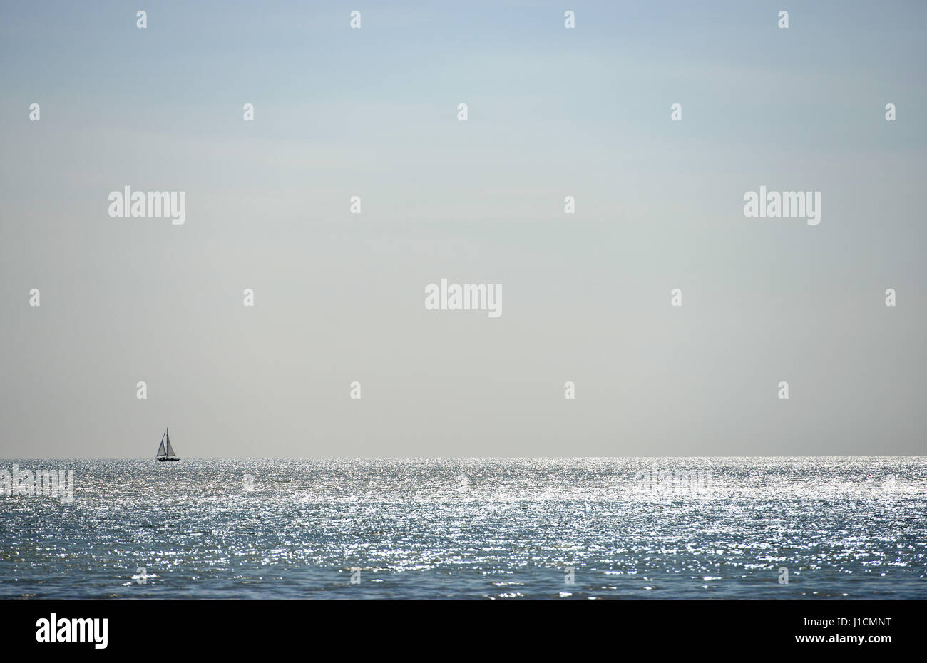 Sail boat dwarfed by sky and sea - Stock Image