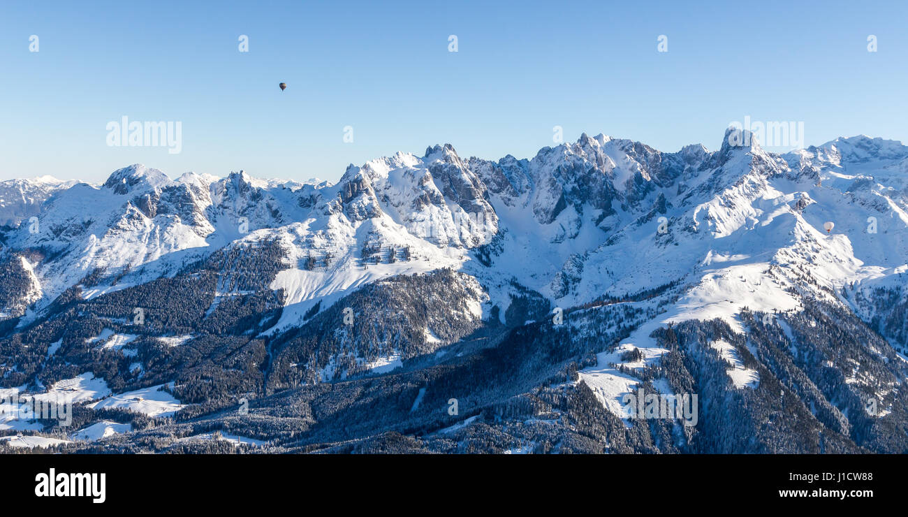 Gosaukamm mountain range in winter with hot air balloon in cloudless blue sky - Stock Image