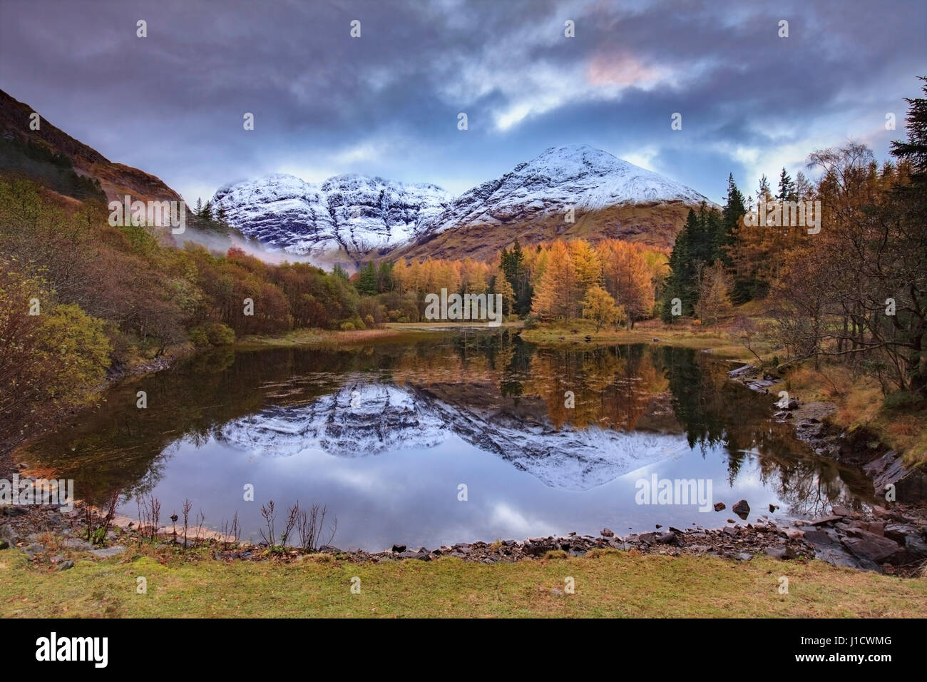 Sunrise at a small lochan in the Pass of Glen Coe with the Three Sisters of Glencoe in the distance. - Stock Image