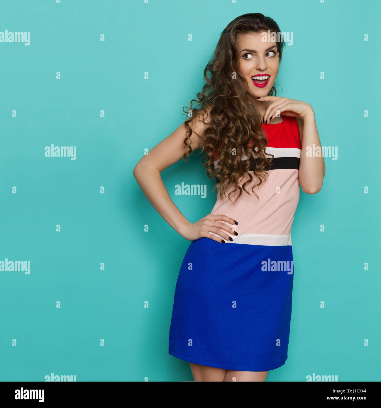 Ecstatic beautiful young woman in colorful mini dress is holding hand on hip and looking away at copy space. Three - Stock Image