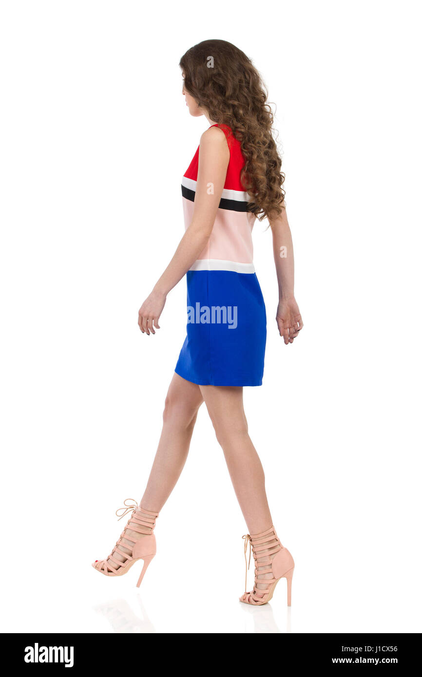 Beautiful young woman in colorful mini dress and high heels is walking and looking away. Side view. Full length - Stock Image
