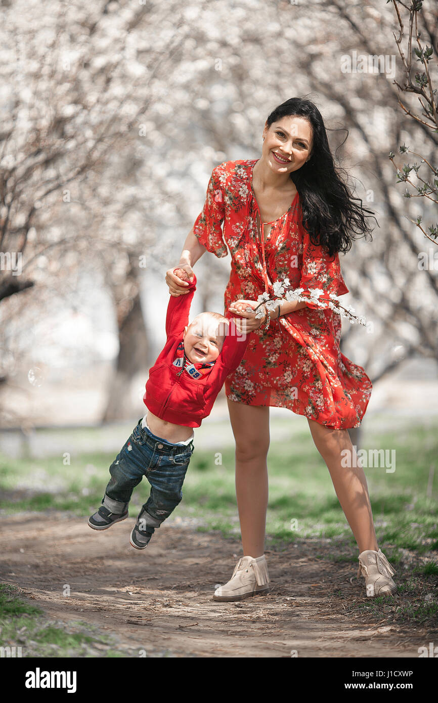 Young mother with her baby on walk in blooming garden. They play and laugh cheerfully among flowering apricot trees. - Stock Image
