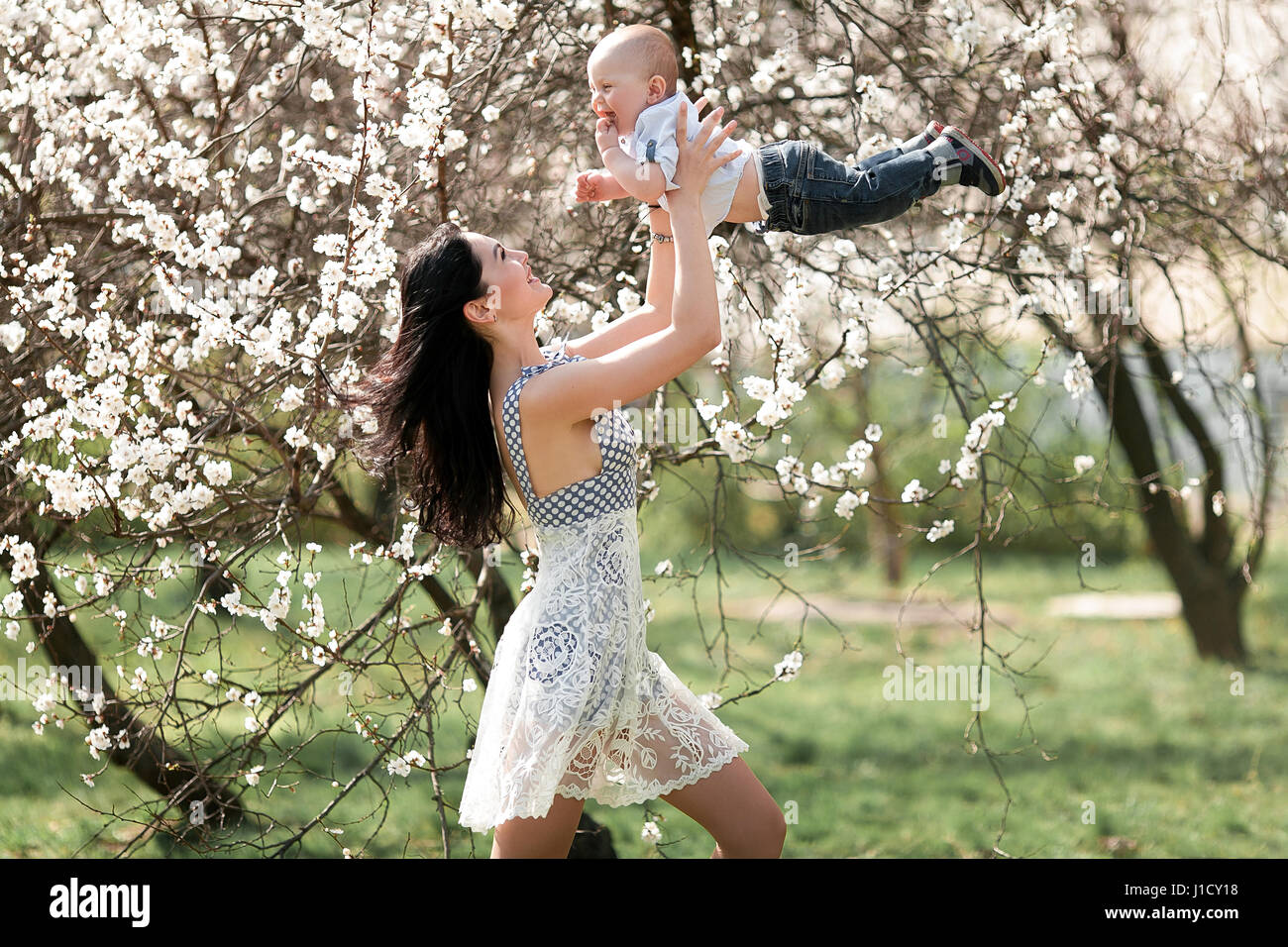 Young mother playing with  her baby on walk in blooming garden. She tosses up baby and they laugh joyful. - Stock Image