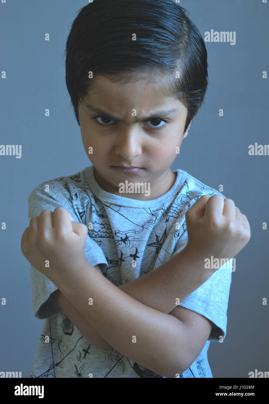 Angry kid ready to fight. Kid crossing arms and showing fists. Unhappy child. Difficult kid. - Stock Image