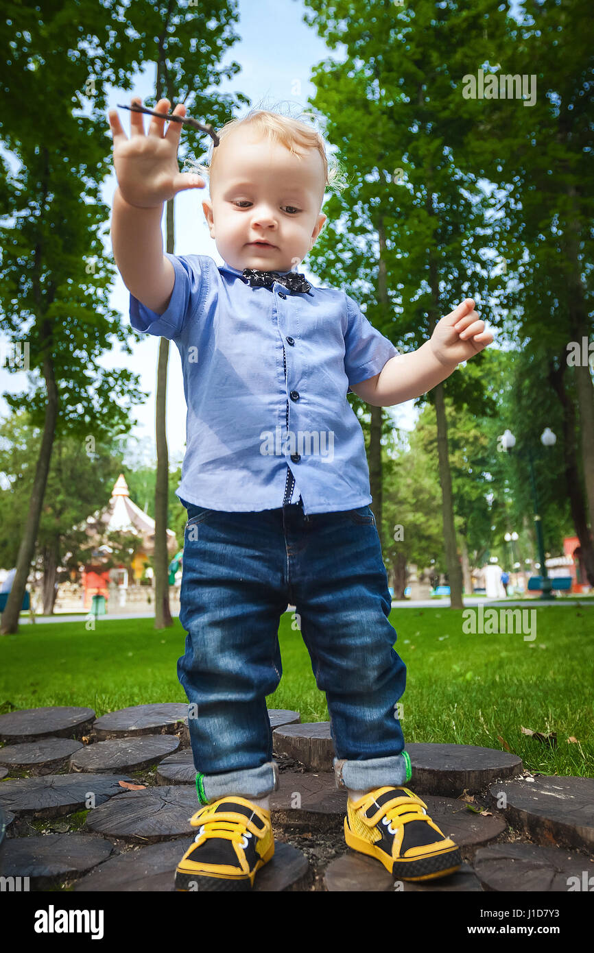 5b779a6a3285 little blonde child in blue shirt, blue pants and black bow tie playing  with branch in city park