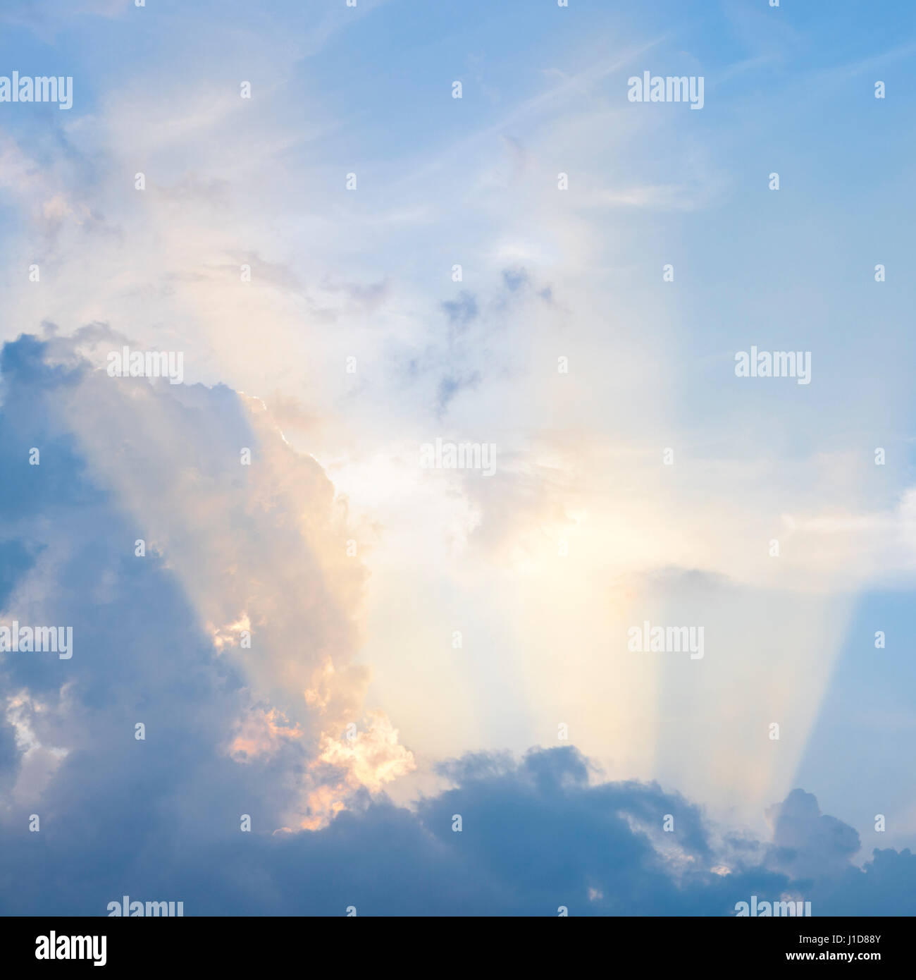 Beams of sunlight from a late evening sun shining through clouds into the blue sky - Stock Image