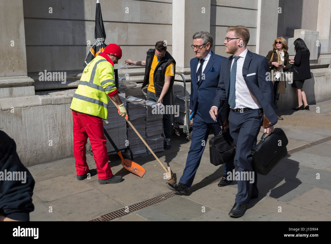 City workers walk past an Evening Standard distributor and a Corporation of London street sweeping contractor. - Stock Image