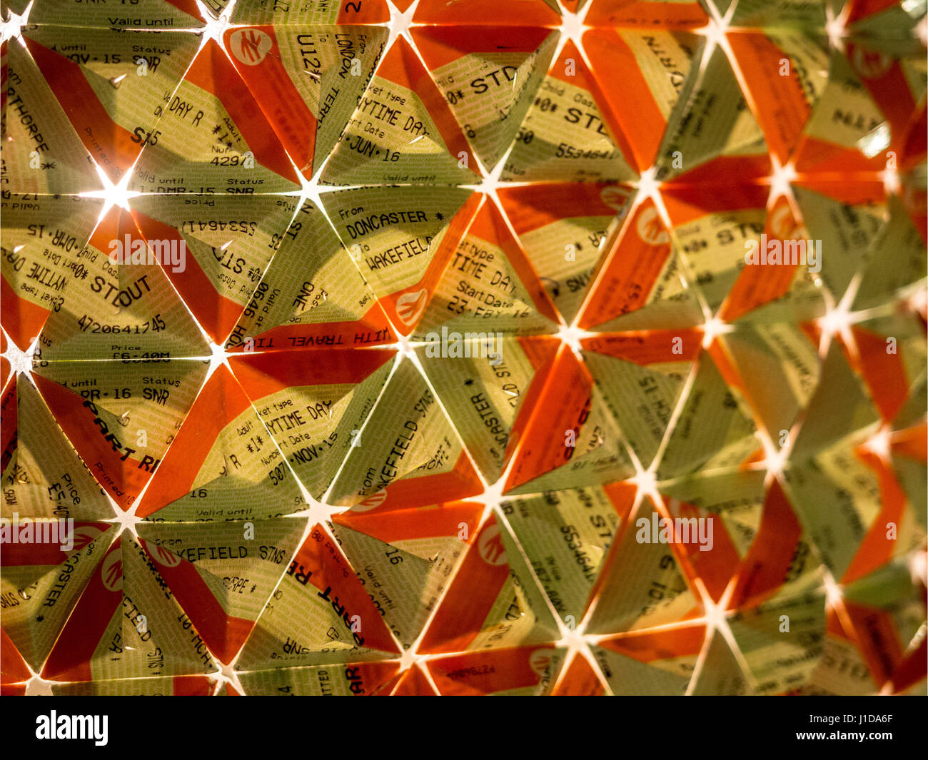 Close up of train tickets folded into triangular pattern with light shining through from behind - Stock Image
